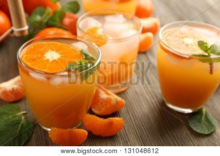 Tangerine cocktails with sliced mandarins, ice, mint on a wooden table, close up