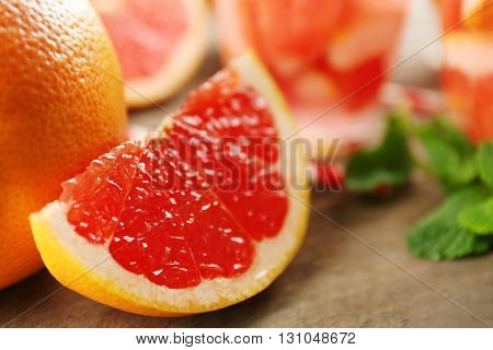 Juicy pieces of grapefruit with fresh mint on wooden table, close up