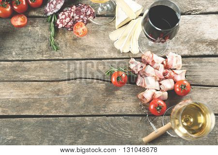 Glass of wine with food on wooden background