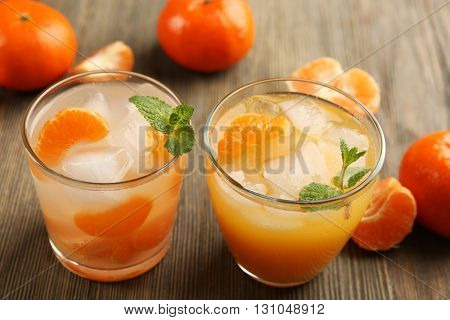 Two fresh delicious tangerine cocktails with ice, mint and mandarins on the wooden table, close up