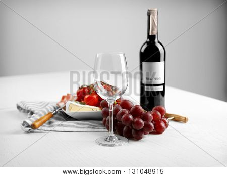 Glass of wine with food on grey background