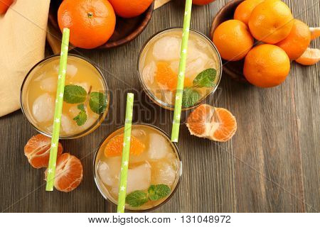 Cocktails with ice, mint and tangerines on the wooden table, top view