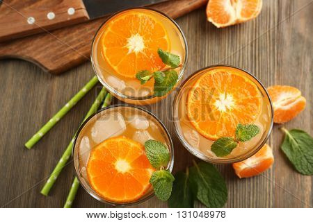 Delicious tangerine cocktails with sliced mandarins, ice, garnished with a mint, served on a wooden table, top view