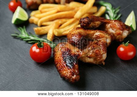 Baked chicken wings with French fries on slate plate
