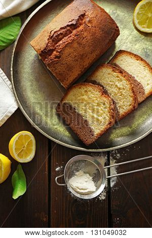 Delicious sweet cake bread in metal tray with lemons on wooden table, top view