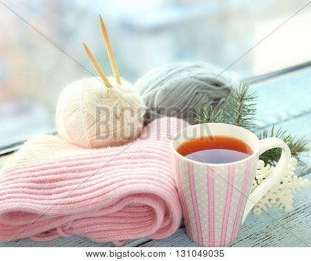 Beautiful winter composition on windowsill with cup of hot drink