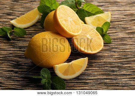 Sliced fresh lemon with green leaves on wooden table closeup
