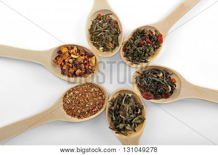 Variety of tea leaves in wooden spoons, isolated on white