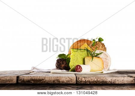 Delicious cheeses on old wooden table, close-up.