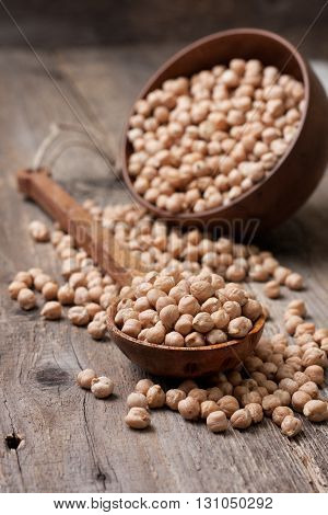 dried chickpeas in a wooden spoon on the old wooden background