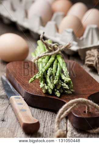 fresh asparagus on a cutting board domestic fresh eggs in a basket on an old wooden background