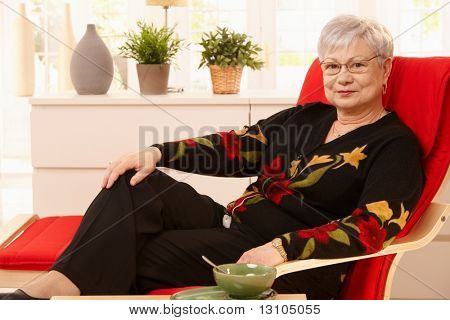 Senior woman relaxing at home, sitting in armchair, having tea.