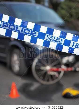 Melbourne, Australia -May 21, 2016: Blue and white Police tape used to cordon off a damaged bicyle under a car and like a crime scene