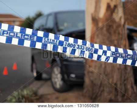 Melbourne, Australia -May 21, 2016: Blue and white Police tape cordoning off a van crushed into a tree like a crime scene