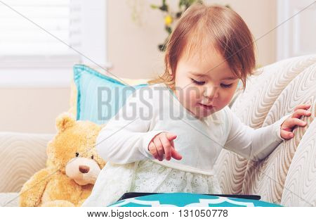 Happy Toddler Girl Watching Her Tablet Computer