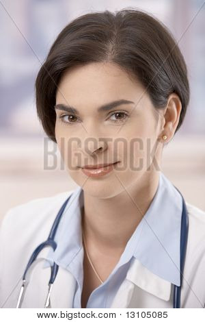 Closeup portrait of attractive young female doctor looking at camera, smiling.