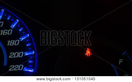 Speedometer and seat belt warning light signals at night.