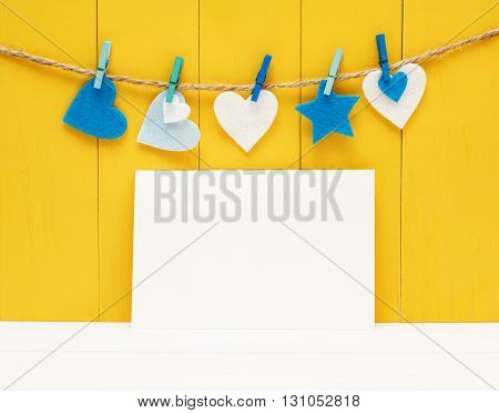 Blank greeting card with felt hearts and yellow wooden background
