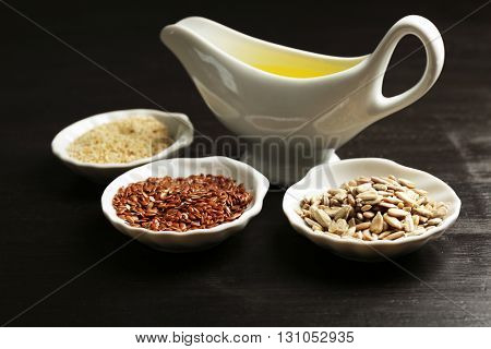 Different kinds of seeds and oil on wooden table