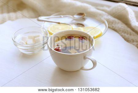 Tea set on a white wooden tray on the windowsill