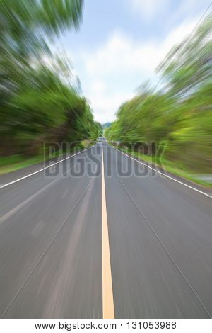 Road in Countryside with zoom blur technique used for high speed motion concept