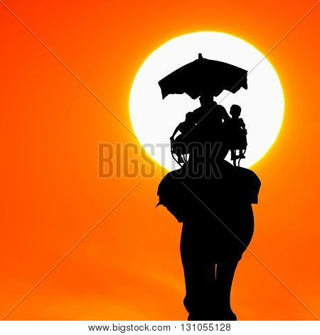 silhouette elephant with tourist at beautiful sunset