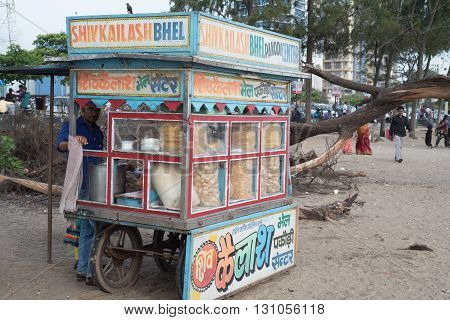 CALICUT INDIA - JULY 30 2015: Young men selling local snacks at stall near Calicut beach side of Kerala India