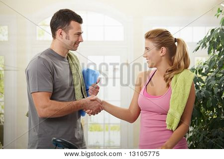 Young woman shaking hands with her personal trainer after training.