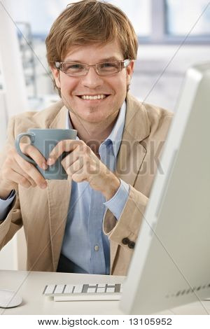 Happy young businessman sitting at office desk, holding coffee cup, smiling.