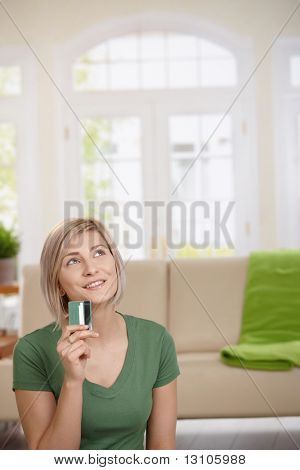Woman sitting at home with credit card in hand dreaming about shopping. Copyspace above.