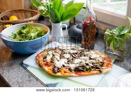 a home made pizza with green salad