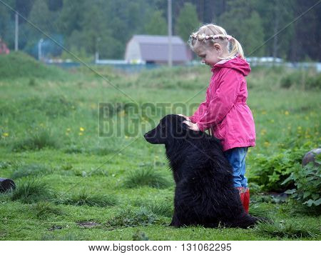 Little girl and big black dog in the rain