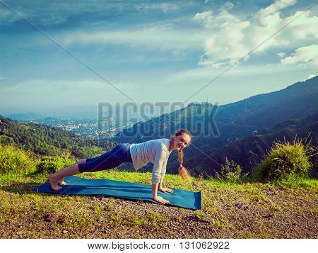 Vintage retro effect hipster style image of woman doing Hatha yoga asana Kumbhakasana plank pose  outdoors in mountains