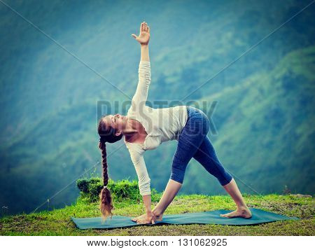 Vintage retro effect hipster style image of woman doing Ashtanga Vinyasa yoga asana Parivrtta trikonasana - revolved triangle pose outdoors