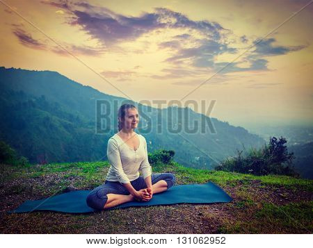 Vintage retro effect hipster style image of sporty fit woman practices yoga asana Baddha Konasana - bound angle pose outdoors in HImalayas mountains on sunset. Himachal Pradesh, India