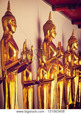 Travel Thailand Buddhism religion - vintage retro effect filtered hipster style image of standing golden Buddha statues close up. Wat Pho temple, Bangkok, Thailand