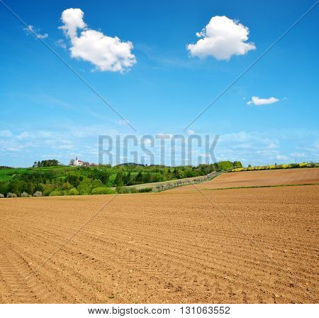 Plowed field in sunny day. Spring rural landscape.