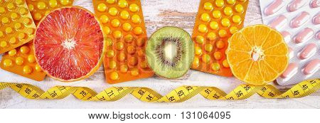 Fresh fruits tape measure and pills tablets or capsules concept of slimming and choice between healthy nutrition and medical supplements