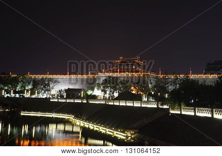 The towers and city wall of of the south gate in Xian lit up at night reflecting off of water in Shaanxi province China.
