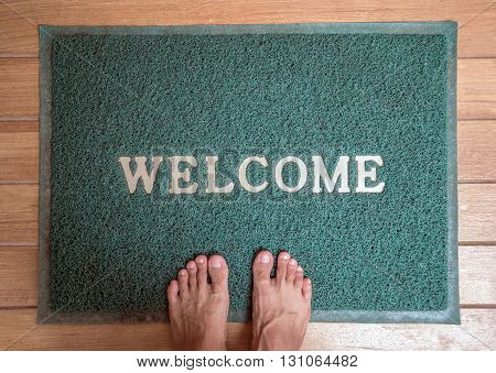 Barefoot standing on foot scraper with welcome word on wooden floor
