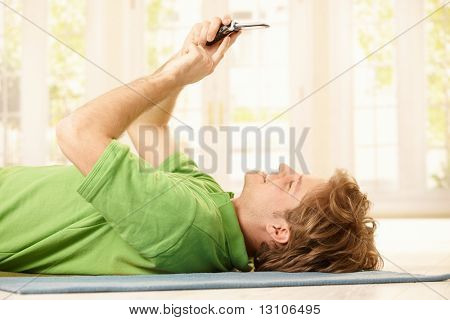 Young smiling man lying on  back on floor in bright room, holding up mobile phone, writing text message.?