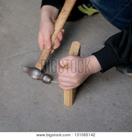 Child Learning To Fix A Nail With The Hammer