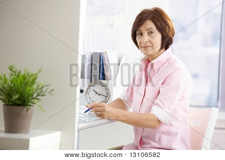 Mature female office worker sitting at desk, taking notes, looking at camera.
