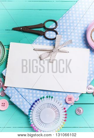 Sewing thread - buttons scissors fabric and empty tag on turquoise wooden background. Selective focus. Scrapbboking. Flat lay. Place for text. Vertical image.