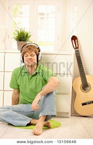 Goodlooking Mann sitzen auf helles Wohnzimmer Boden neben Gitarre, Musik über Kopfhörer hören