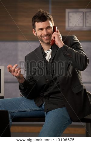 Happy businessman laughing making landline phone call, gesturing with hand, sitting on office desk.