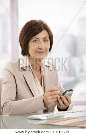 Portrait of smiling female businesswoman holding smartphone, looking at camera.