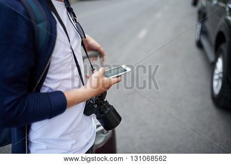Close-up image of traveler using application on his smartphone