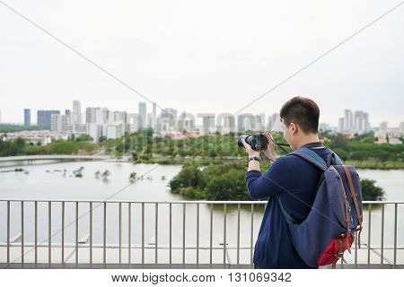 Rear view of Vietnamese guy taking photo of city across the river