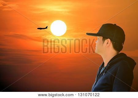 Asian man wearing a blue long sleeve shirt and wearing a hat looking at the airplane on the red sky with beautiful sunlight.